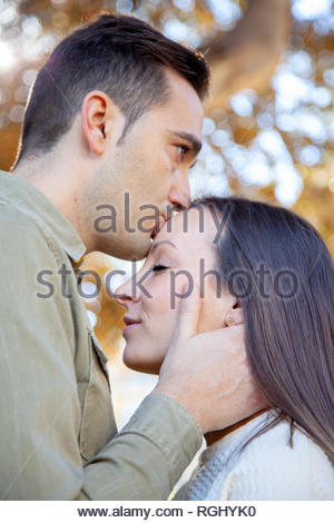 Man kisses in the forehead of his girlfriend in a public park at daylight in an European city - Stock Image