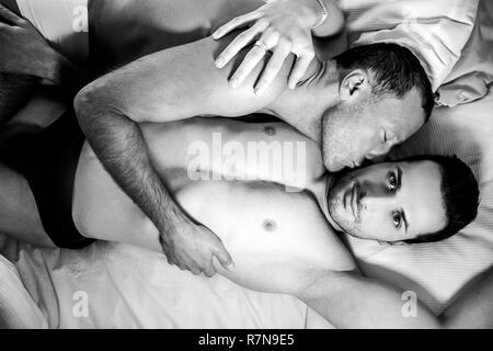 Handsome male gay couple lying together in bed, one kissing other looking at camera - Stock Image