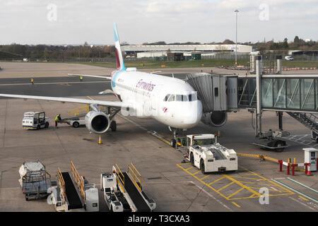 A Eurowings Airbus A319 docked at an air bridge at Birmingham International Airport, England - Stock Image