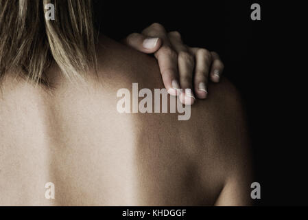 Woman rubbing her bare shoulder, cropped - Stock Image