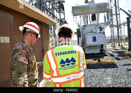 SGT Dalton Rezac (L), B Co., 249th Engineer Battalion (Prime Power), talks with member of the Puerto Rico Aqueducts and Sewers Authority, about how power gets to La Plata Lake Dam, Toa Alta, Puerto Rico, August 28, 2018.    The Corps of Engineers continues to work as part of a unified effort with it partners at the federal, state and local agencies to help the U.S. citizens of Puerto Rico recover from this disaster. - Stock Image