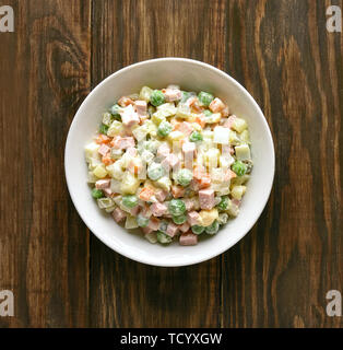 Bowl of traditional russian salad 'Olivier' from boiled vegetables and sausage with mayonnaise. Russian New Year or Christmas salad on wooden backgrou - Stock Image