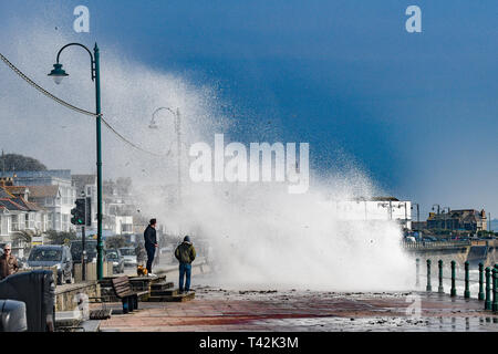 Penzance, Cornwall, UK. 13th Apr, 2019. UK Weather. Despite the sunshine it felt cold on the sea front at Penzance, as the 50mph wind pushed waves over the promenade on the seafront. Credit: Simon Maycock/Alamy Live News - Stock Image