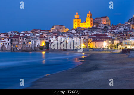 Beautiful view of the beach, Cefalu Cathedral and old town of coastal city Cefalu during evening blue hour, Sicily, Italy - Stock Image