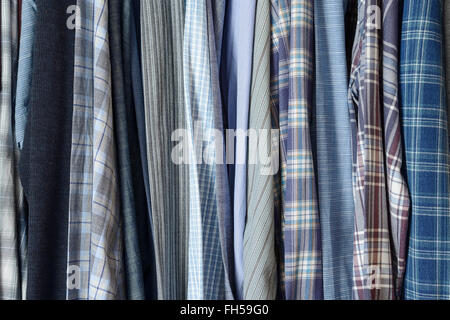 Blue patterned shirts in a wardrobe - Stock Image