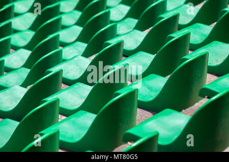 Green plastic seats in rows in an empty stadium. - Stock Image