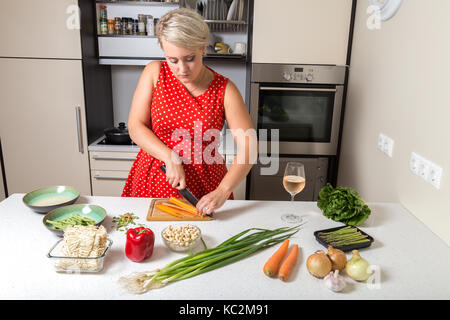 Girl cutting carrot and preparing for vegetable wok - Stock Image
