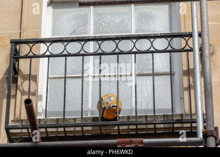 An orange football caught in an iron window balcony surround for a frosted glass window with some scaffolding just visible - Stock Image
