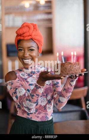 Portrait confident young woman carrying birthday cake - Stock Image