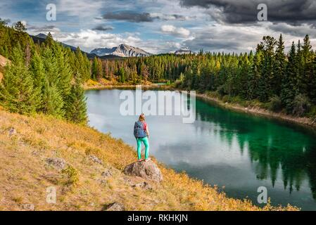 Young hiker at a lake, Fourth Lake, Valley of the Five Lakes, Jasper National Park, back mountains, Alberta, Canada - Stock Image