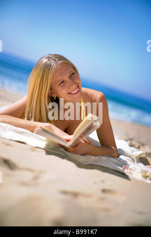 Girl on beach reading a book - Stock Image