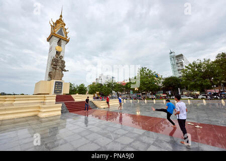 A group of boys play football in front of the Cambodia-Vietnam Friendship Monument in Botum Park, Phnom Penh, Cambodia. - Stock Image