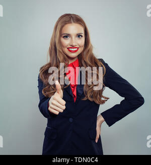 Smiling woman showing thumb up on white - Stock Image