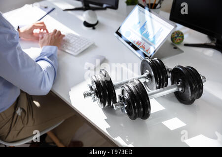 Close-up Of Dumbbells In Front Of Businessperson Working In Office - Stock Image