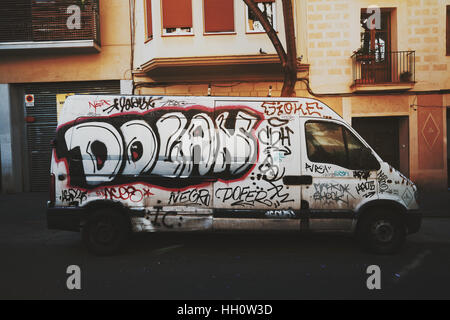 Abandoned car slovenly painted with graffiti parked on the street of european city with residential house behind - Stock Image
