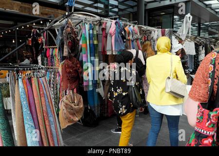 Rear back view of women walking near a scarf stall 'Kashimi Scarves' in Spitalfields Market near Brick Lane in East London E1 UK  KATHY DEWITT - Stock Image