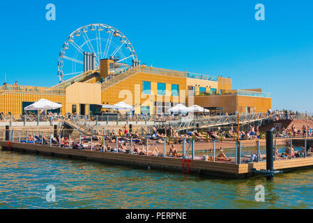 Helsinki summer city, view of Finnish people relaxing in the Allas Sea Pool on a summer afternoon, Helsinki harbor, Finland. - Stock Image