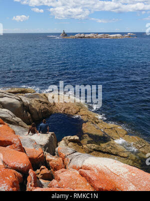 Couple at rockpool at Sloop Reef, Bay of Fires, Tasmania, Australia. No MR - Stock Image
