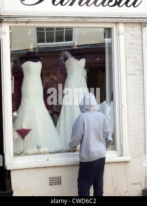 Teenage girl wearing a hoodie looking into a bridal shop window at wedding dresses, Abingdon, Oxfordshire. Model - Stock Image