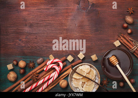 Winter spices and ingredients for cooking. Cinnamon sticks, hazelnuts, walnuts, nutmeg, cloves, anise stars on an old wooden background (top view) - Stock Image