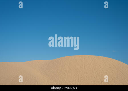 beautiful sand dunes against bright blue sky background. concept of nature background, travel, holiday and climate - Stock Image