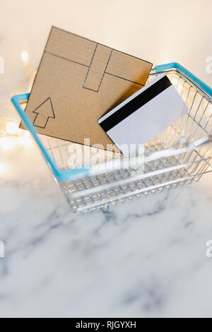 payment card and mini cardboard delivery icon in shopping basket, concept of ordering and receiving your purchases - Stock Image