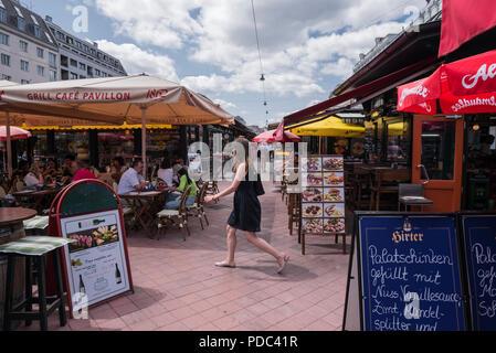Young woman walking through Naschmarkt restaurants, Vienna, Austria - Stock Image
