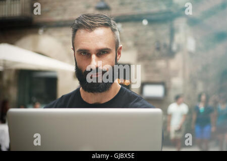 Closeup Portrait Handsome Bearded Businessman Wearing Black Tshirt Working Laptop Urban Cafe.Young Manager Work - Stock Image