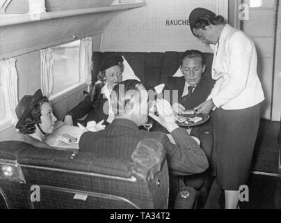 Passengers in the smoking compartment of a Focke-Wulf FW 200 'Condor' of the Deutsche Lufthansa. The aircraft was registered D-AETA, and its given name is 'Westfalen'. - Stock Image