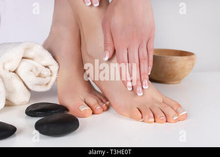 Female bare feet and hands with french manicure and pedicure in beauty salon with towel and decoration stone and wooden bowl. Beauty and spa concept - Stock Image