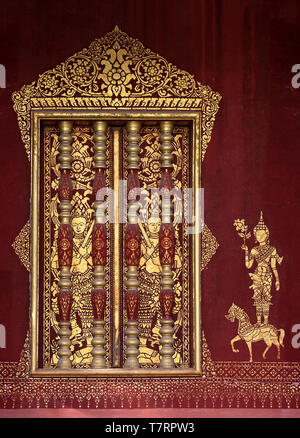 Windows accented with Khmer-style wooden balustrades and gilded murals stencils of a deity, Temple Wat Sensoukharam,  Luang Prabang, Laos - Stock Image
