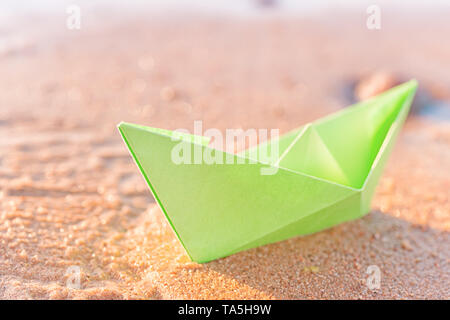 Green paper boat on sandy beach outdoors. Selective focus on the boat - Stock Image