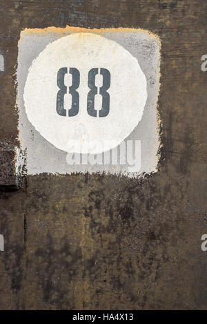 Aged and worn vintage number 88 in a white circle, inside a grey square, and on a back grunge style background - Stock Image