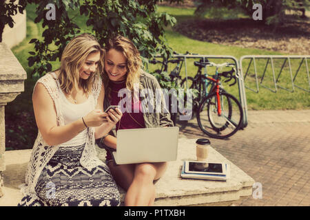 Two female university students sitting together and using their smart phone and laptop computer while sitting on the steps of a campus building - Stock Image