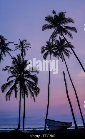 Silhouettes of palm trees against a sunset over the sea with a boat in the foreground. - Stock Image