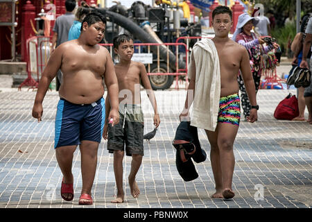 Thailand boys walking shirtless along the street. Three young friends outside. Southeast Asia - Stock Image