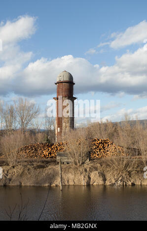 Stacks of pulp grade logs line the mill road, on the yard, at Fodge Pulp Products, with the old Bonners Ferry Lumber Company waste furnace tower in th - Stock Image