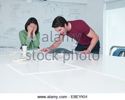 Businesswoman yelling into teleconferencing equipment in conference room - Stock Image
