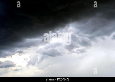 Stormy clouds in the sky with shades of black and grey and fragments and wisps of rain - Stock Image