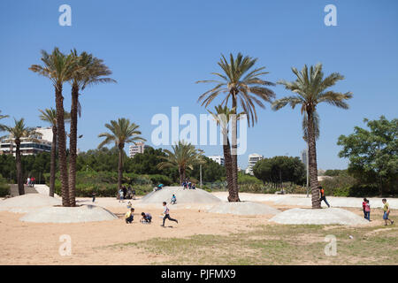 Children playing between palm trees and concrete dunes in the park called The desert located at 200m of the Palestinian camp of Shatila, Beirut, Lebanon - Stock Image