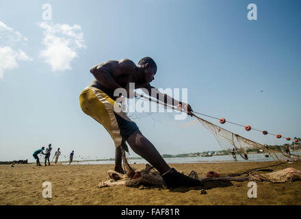 A fisherman pulls in his catch on a beach in Freetown, Sierra Leone. - Stock Image