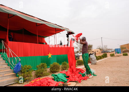 A soldier from Burkina Faso prepares a stand with the colours of the country's national flag in preparation for the closing ceremony of Flintlock 2019 - Stock Image