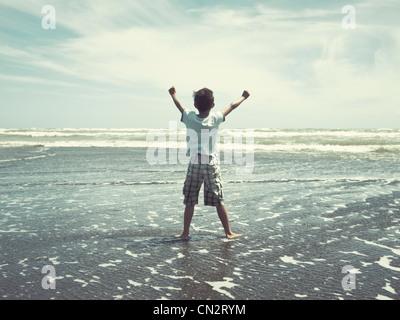 I hold back the sea: boy on beach, New Zealand. - Stock Image