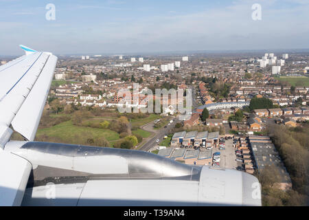 An aerial view across Birmingham as a passenger jet comes in to land at Birmingham International Airport - Stock Image