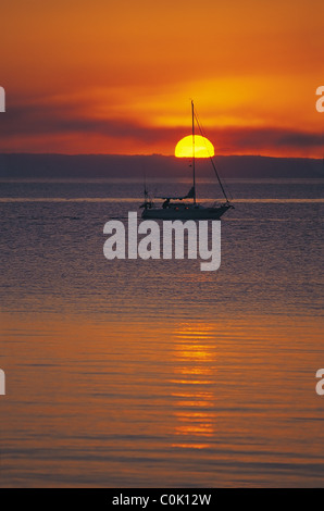 Yacht silhouetted by setting sun - Stock Image