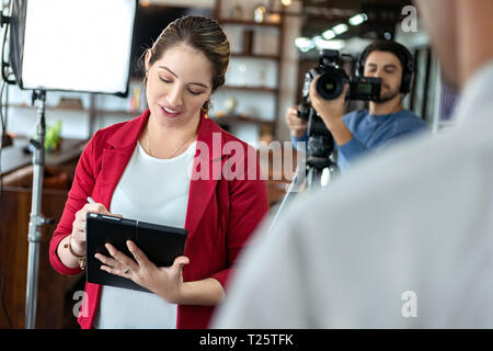 Happy businessman during corporate interview with female journalist. Manager answering question in office. Young woman at work as reporter with busine - Stock Image