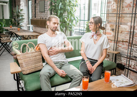 Man having abdominal pain sitting during the conversation with young woman on the sofa indoors - Stock Image