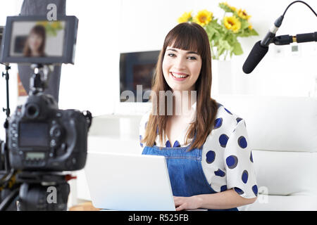 Portrait Of Female Vlogger Recording Broadcast At Home - Stock Image