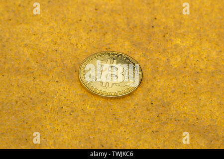 one bitcoin crypto coin on a shiny golden sand background with backlight - Stock Image