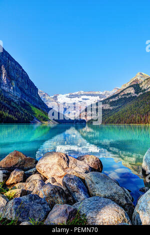 Lake Louise in Banff National Park with its glacier-fed turquoise lakes and Mount Victoria Glacier in the background. Visitors paddling red canoes in  - Stock Image